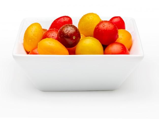 Bol de tomates cerises colorées (rouge, grenat et jaune), fraîches et crues. avec des gouttes d'eau isolé sur fond blanc