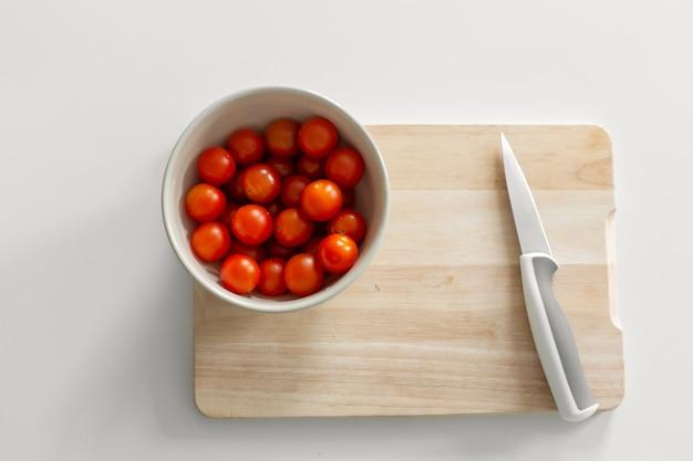 Un bol de tomates cerises sur une planche à découper. cuisiner des aliments sains et savoureux