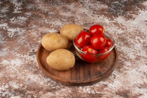 Bol de tomates marinées et pommes de terre bouillies sur plaque en bois.