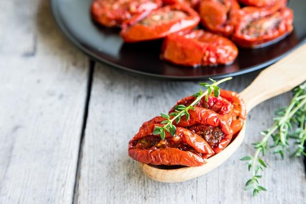 Bol de tomates séchées au soleil sur fond en bois. tomates séchées à l'huile d'olive et aux herbes