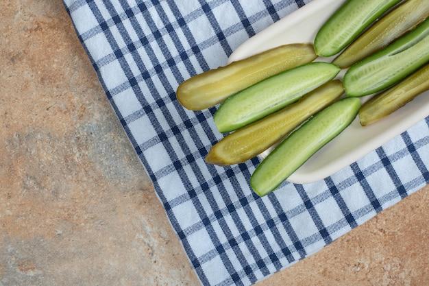 Bol de tranches de concombre mariné et frais sur nappe