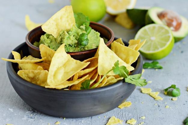Bol de trempette au guacamole avec nachos de maïs (chips) et ingrédients sur fond bleu, mise au point sélective. plat national mexicain.