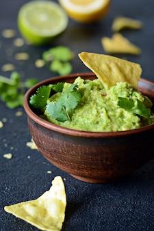 Bol de trempette au guacamole avec nachos de maïs (chips) et ingrédients sur fond sombre, mise au point sélective.