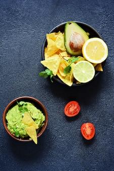 Bol de trempette au guacamole avec nachos de maïs (chips) et ingrédients. plat national mexicain.