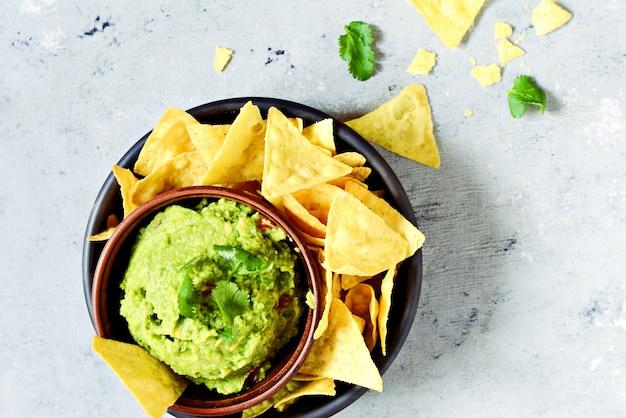 Bol de trempette au guacamole avec nachos de maïs (chips) et ingrédients, selective focus