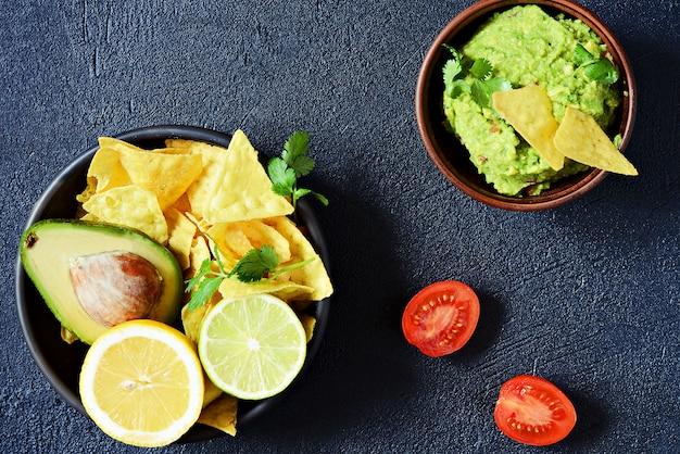 Bol de trempette au guacamole avec nachos de maïs (chips) et ingrédients