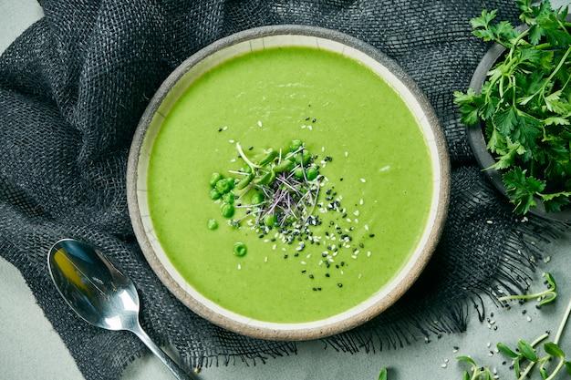 Bol végétarien avec soupe à la crème verte de brocoli et de pois verts sur un tissu gris. vue de dessus plat alimentaire