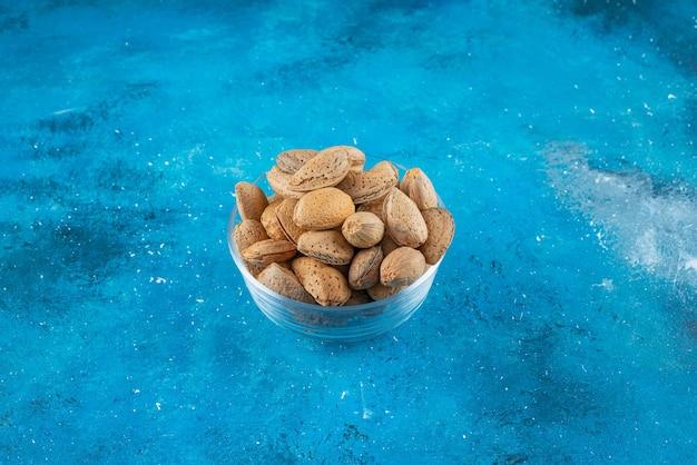 Un bol en verre d'amandes décortiquées sur la surface bleue