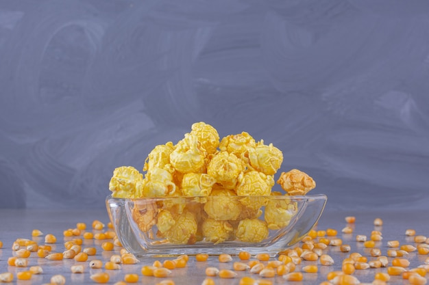Bol en verre de délicieuses boules de maïs sur table en pierre