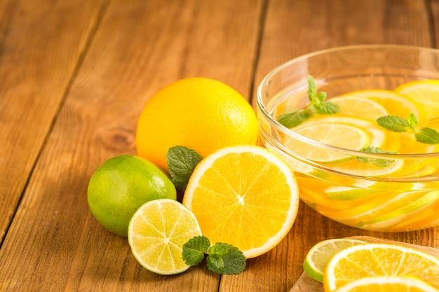 Bol en verre avec de l'eau détox avec des tranches d'orange et de citron vert.