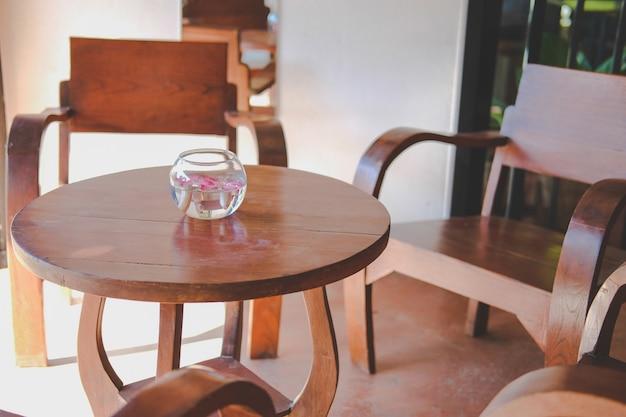 Bol en verre avec fleur flottant sur la décoration de l'eau sur une table en bois dans le salon à la maison