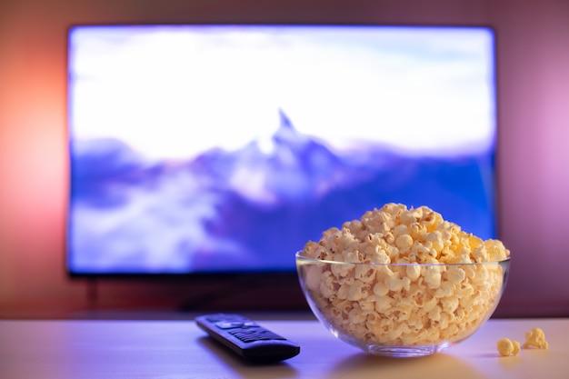 Un bol en verre de maïs soufflé et télécommande.