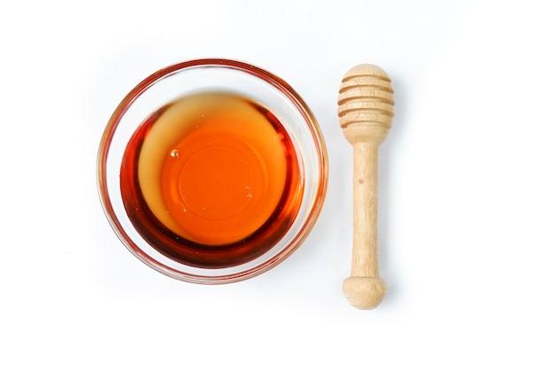 Bol en verre de miel pur avec une cuillère en bois de miel isolé sur fond blanc