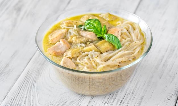 Bol en verre de nouilles au curry vert décoré de basilic frais