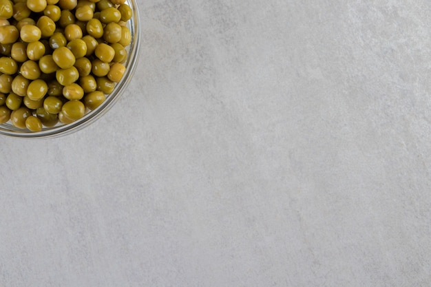 Un bol en verre plein de petits pois frais placés sur une table en pierre.