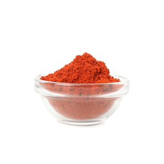 Bol en verre avec de la poudre de poivron rouge isolé sur blanc