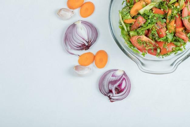 Bol en verre de salade de légumes frais sur fond blanc.