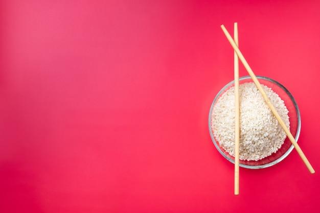 Bol en verre transparent à plat avec du riz et des baguettes sur fond rose