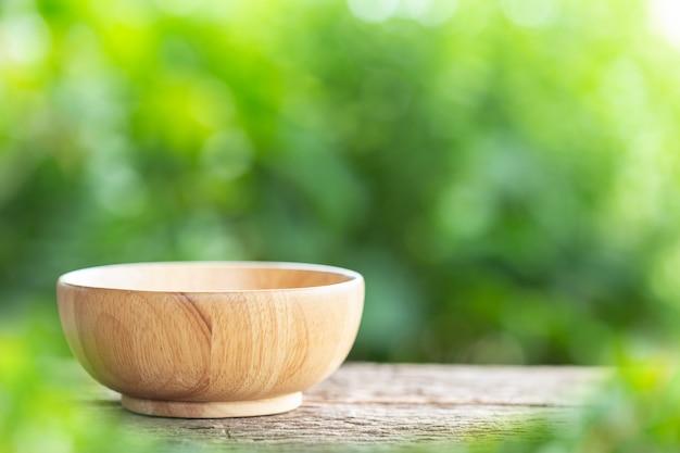 Bol vide sur une table en bois avec un fond clair flou vert