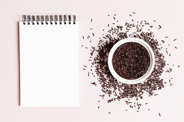 Bol vue de dessus avec du chocolat et cahier