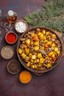Bol de vue rapprochée avec bol de nourriture avec champignons frits et pommes de terre différentes épices et huile à côté des branches et des cônes