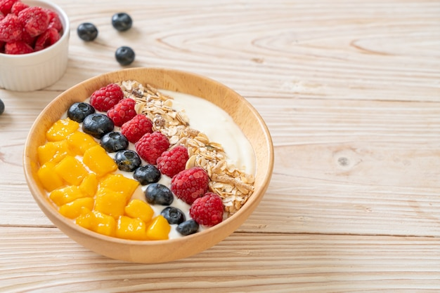 Bol de yaourt fait maison avec framboise, myrtille, mangue et granola - style alimentaire sain