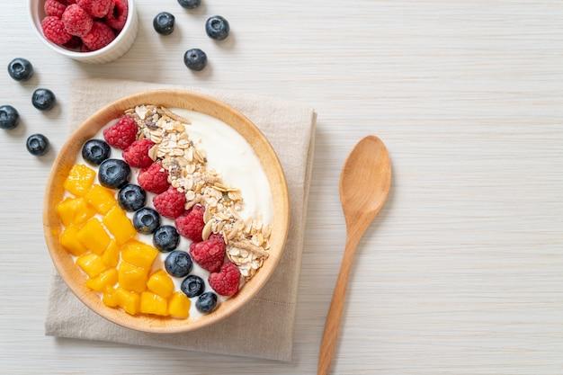 Bol de yogourt fait maison avec framboise, myrtille, mangue et granola - style alimentaire sain