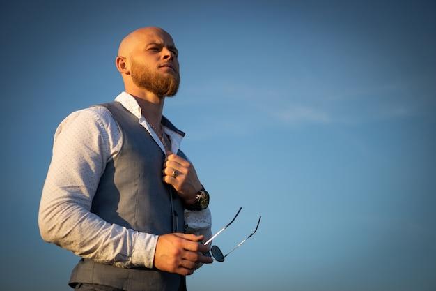 Bold guy avec une barbe élégante et des lunettes de soleil sur un ciel au coucher du soleil. concept de succès et de volonté.