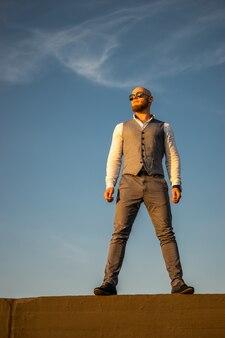 Bold guy avec une barbe élégante et des lunettes de soleil sur une surface du ciel au coucher du soleil