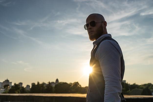 Bold guy avec une barbe élégante et des lunettes de soleil sur une ville floue pendant le coucher du soleil. concept de succès et de volonté.