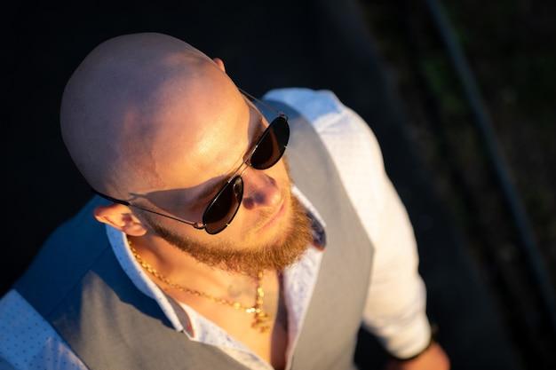 Bold guy avec une barbe élégante et des lunettes de soleil