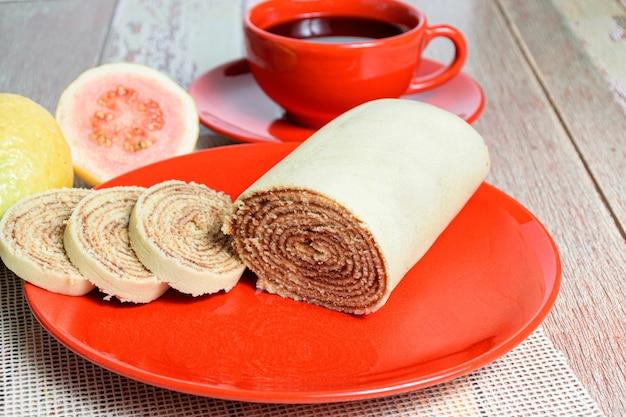 Bolo de rolo (gâteau roulé) à côté de goyaves et d'une tasse de café rouge.
