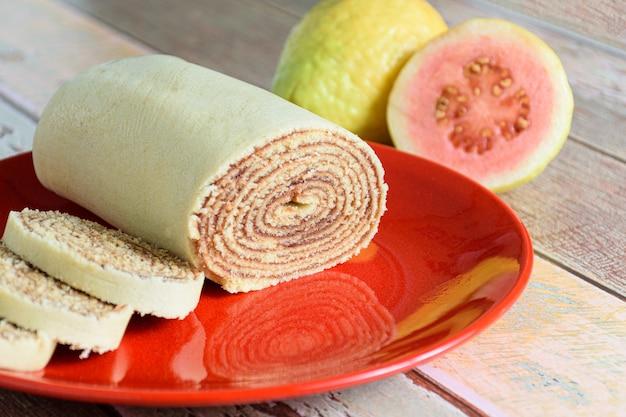 Bolo de rolo (gâteau roulé) tranché sur une assiette rouge à côté de goyaves.