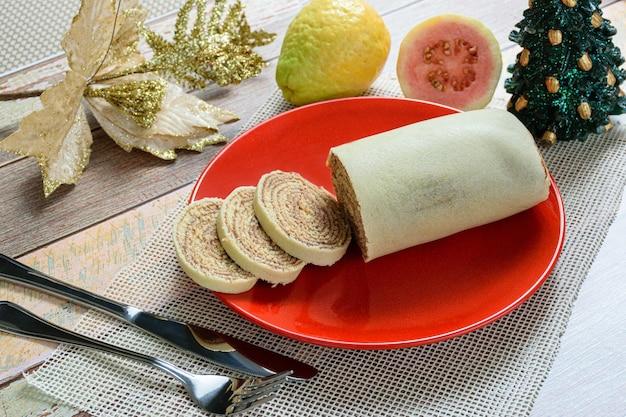Bolo de rolo (gâteau roulé) tranché aux côtés de couverts, décoration de noël et goyaves.