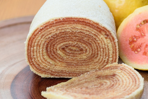 Bolo de rolo sur une planche de bois à côté de goyaves