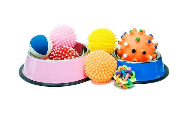Bols en acier inoxydable et jouets en caoutchouc pour animaux de compagnie sur fond blanc isolé.