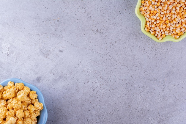 Bols alignés de manière opposée remplis de grains de maïs et d'un tas de maïs soufflé au caramel sur fond de marbre. photo de haute qualité