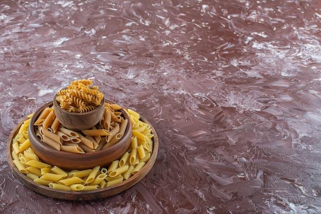 Bols en argile de pâtes crues penne et fusilli sur surface en marbre