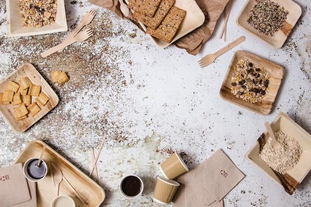 Bols, assiettes, verres, fourchettes, serviettes de table et différents ustensiles en plastique présentés autour d'une table avec différents ingrédients, café et lait