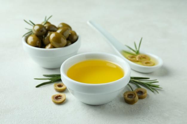 Bols aux olives et huile sur blanc texturé