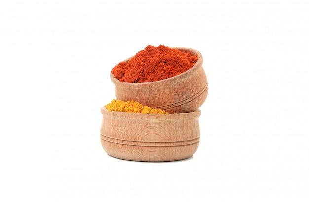 Bols en bois avec du poivron rouge et de la poudre de curcuma isolé sur blanc