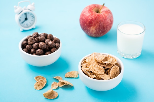 Des bols avec des boules de céréales et de chocolat, un verre de lait, une pomme et un réveil sur une table bleue. petit déjeuner programmé