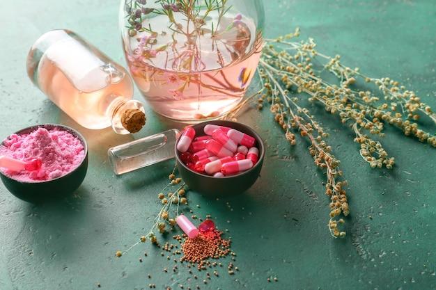 Bols avec capsules, poudre et verrerie d'huile essentielle sur table de couleurs
