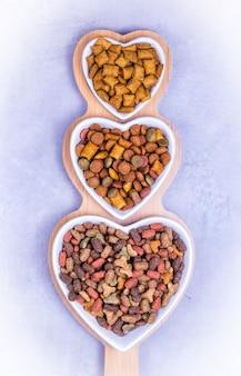 Bols coeur avec nourriture sèche pour chat