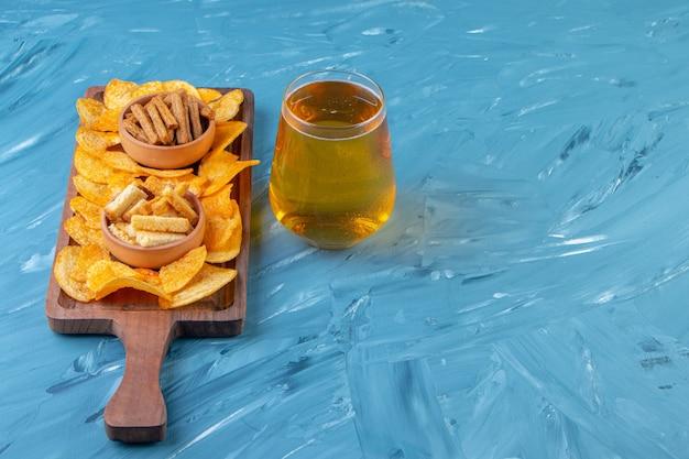 Bols de croûtons et chips sur une planche à côté d'une chope de bière , sur fond bleu.