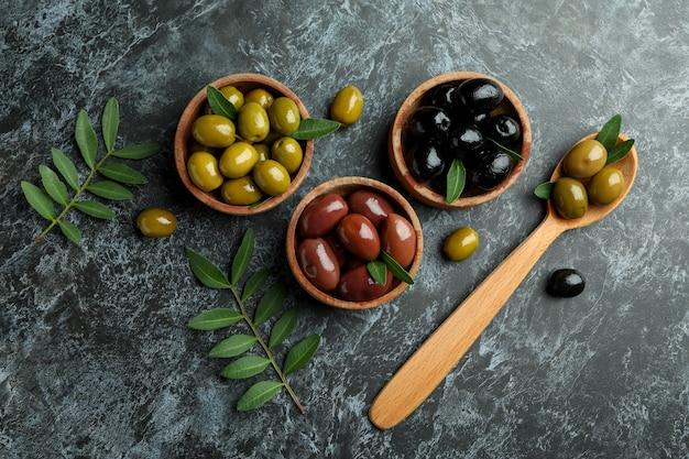 Bols et cuillère aux olives sur fond isolé smokey noir