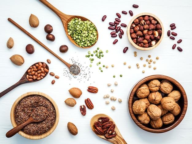Bols et cuillères de diverses légumineuses et différentes sortes de noix sur une table en bois.