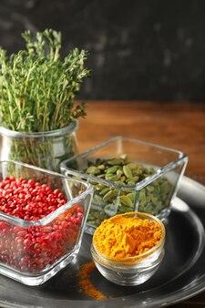 Bols avec différentes épices aromatiques et thym sur plateau en métal