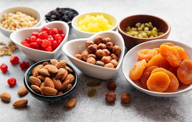 Bols avec divers fruits secs et noix sur une surface de béton gris