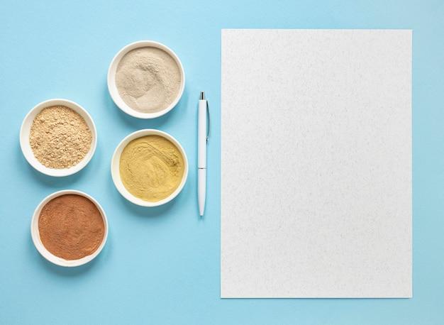 Bols avec du sable coloré et du papier espace copie